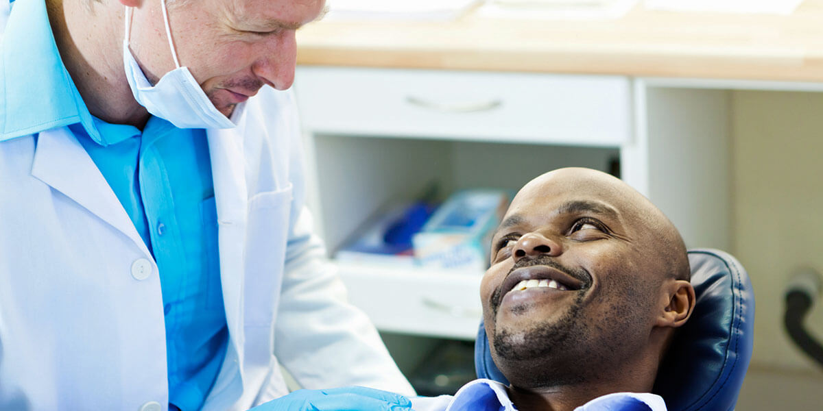 Doctor speaking with patient in dental chair